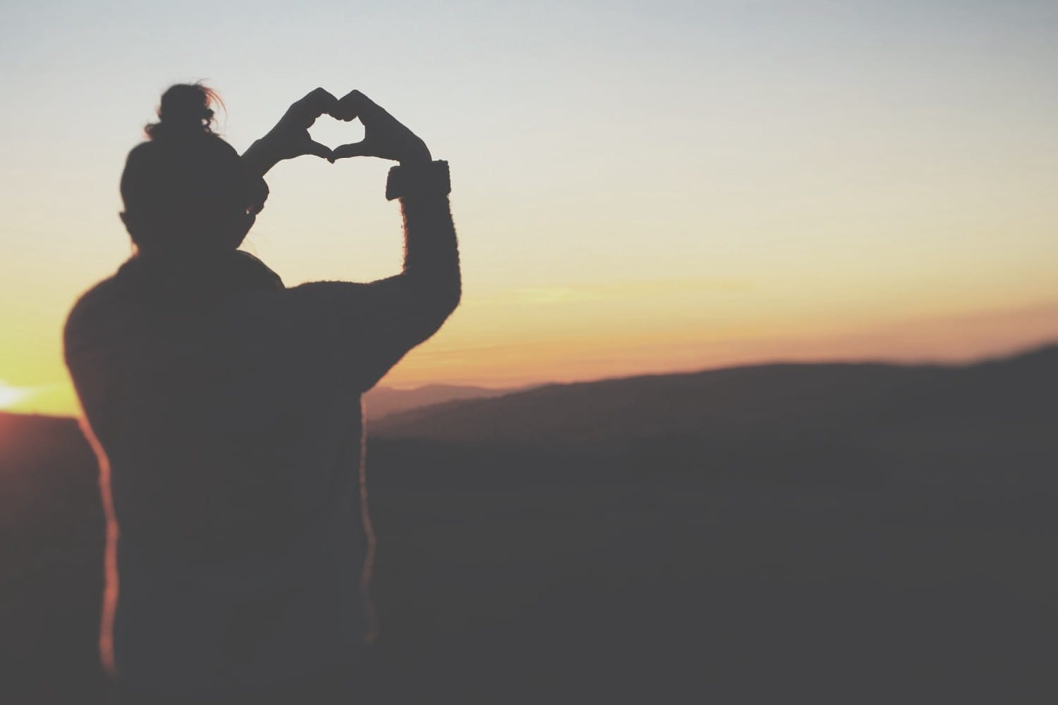 a girl watching the sunset making a heart shape with her hands