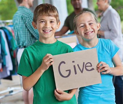 Kids holding a sign that says Give