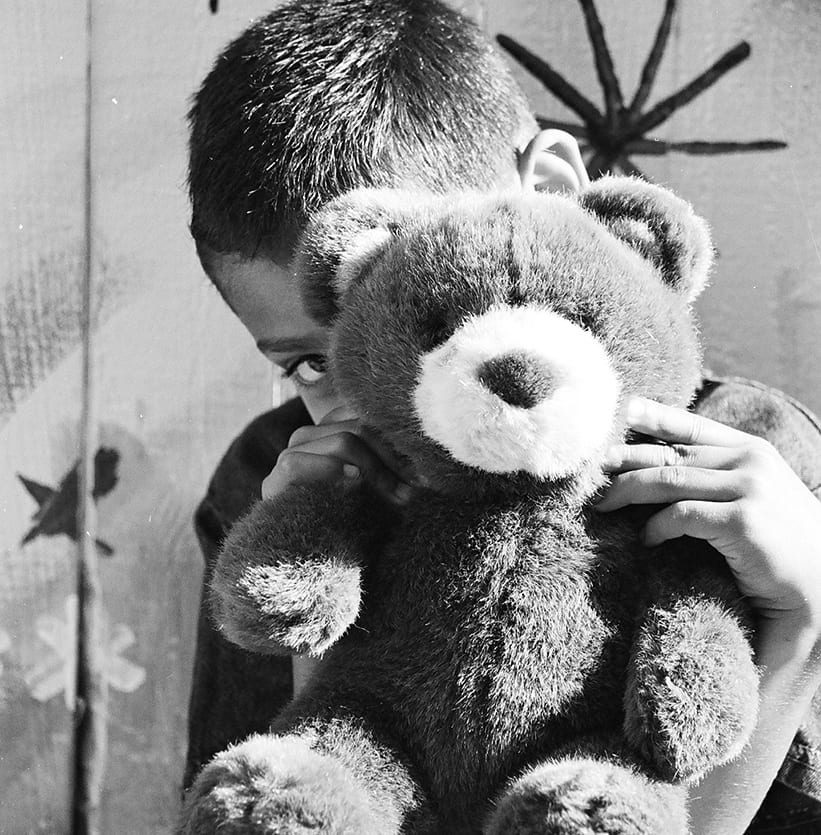 Young boy taking shelter with teddy bear