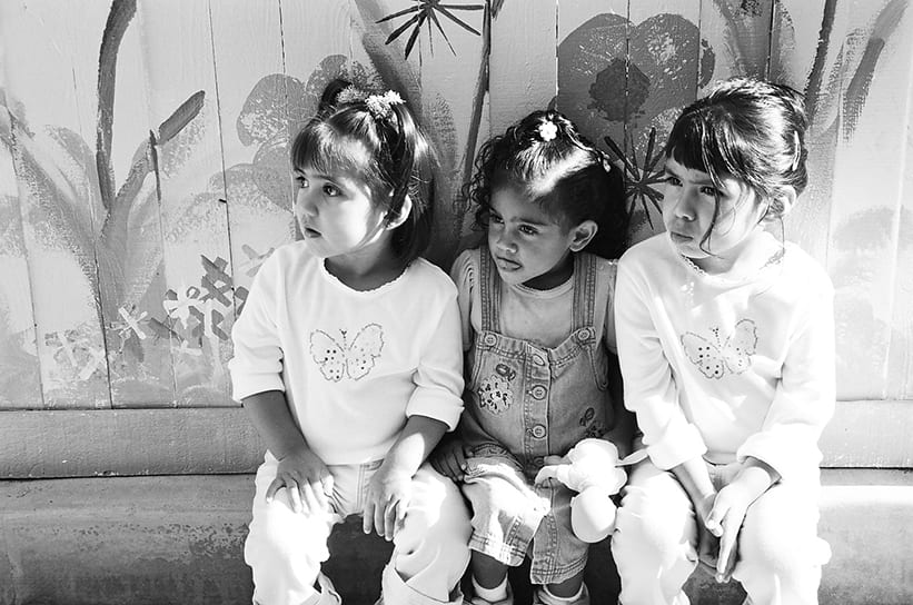Three young girls sitting on a bench